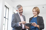 Two colleagues with digital tablet in an office - RBF001861