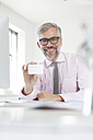 Portrait of smiling man at desk showing his business card - RBF001828