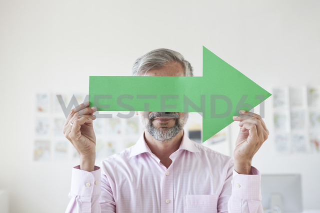 Businessman covering his eyes with a green arrow - RBF001892