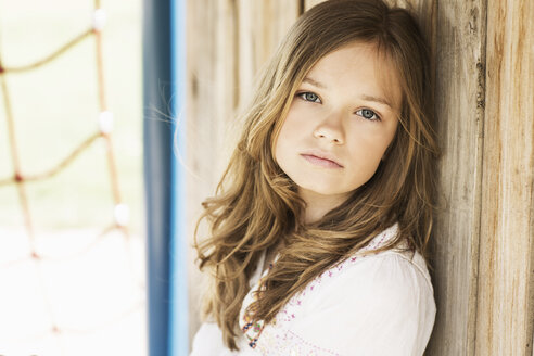 Portrait of sad girl leaning against wooden wall - GDF000420