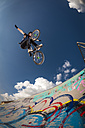 Germany, Young man performing stunt on BMX bike - KJ000309