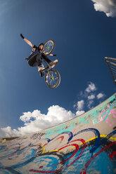 Germany, Young man performing stunt on BMX bike - KJ000309