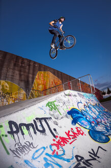 Germany, Young man performing stunt on BMX bike - KJ000312