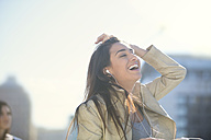 Portrait of laughing woman with earphones listening music - ZEF000774