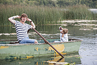 Germany, Rhineland-Palatinate, Laacher See, playful father and son in boat - PAF000917