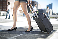 Legs of young woman walking with rolling suitcase - ZEF000781