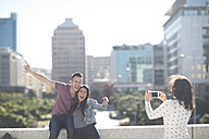 Woman photographing happy young couple with smartphone - ZEF000807