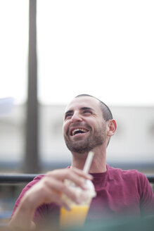 Portrait of laughing man having a break with soft drink - ZEF000330