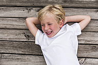 Portrait of laughing little boy lying on a jetty - DAWF000112