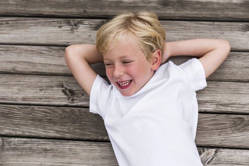 Portrait of laughing little boy lying on a jetty - DAWF000112