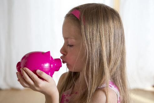 Little girl kissing her pink piggy bank - SARF000815
