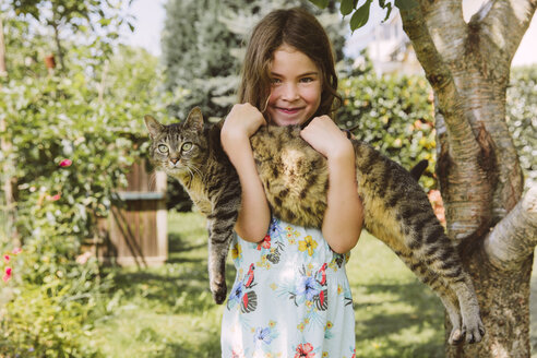Girl holding cat in garden - MFF001267