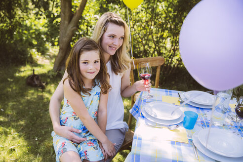 Daughter sitting on mother's lap at garden party table - MFF001241