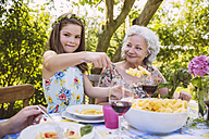 Girl serving pasta to grandmother at garden party - MFF001251