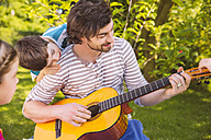 Father with children playing guitar in garden - MFF001325