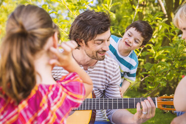 Father with children playing guitar in garden - MFF001304