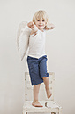 Portrait of smiling little boy with angle wings standing on a chair - MJF001337