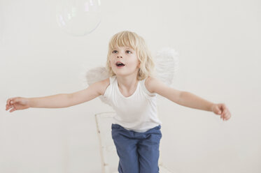 Portrait of gaping little boy with angle wings watching a soap bubble - MJF001341