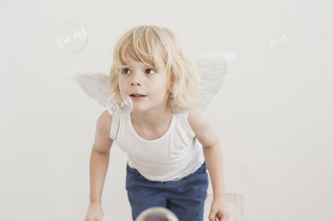 Portrait of little boy with angle wings watching soap bubbles - MJF001343