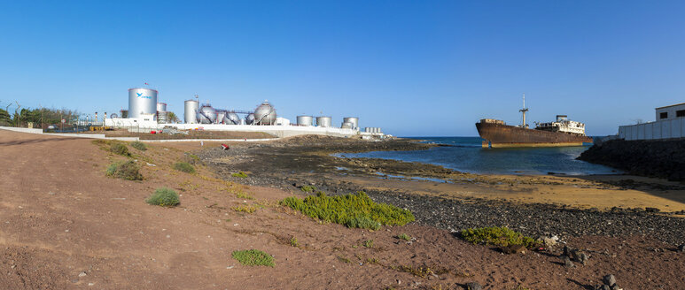 Spain, Canary Islands, Lanzarote, Arrecife, Punta Chica, Ship wreck Telamon, Industrial plant of Disa company in the background - AMF002790