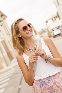 Spain, Mallorca, portrait of smiling young woman wearing sunglasses - JUNF000028