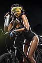 Woman with mountain bike and water bottle in front of black background - MAEF009056