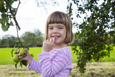 Portrait of smiling little girl holding twig of a pear tree - LVF001800