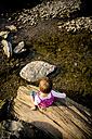 Little girl sitting on deadwood at riverside - LVF001789