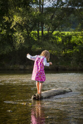 Little girl balancing on a rock in a river - LVF001803