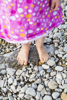 Feet of little girl standing on pebbles at riverside - LVF001791