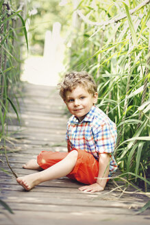 Portrait of little boy sitting on walkway - AFF000071