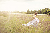 Happy bride wearing white wedding dress walking on a meadow - AFF000073