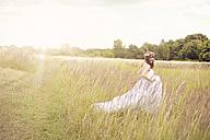 Happy bride wearing white wedding dress walking on a meadow - AFF000073