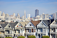 USA, California, San Francisco, Victorian houses at Alamo Square in front of the skyline - BRF000691