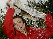 Portrait of young woman at rainfall holding newspaper over her head - BFRF000509