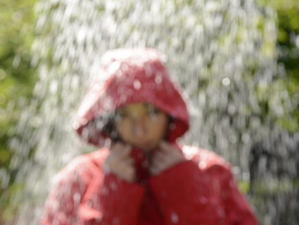 Blurred portrait of young woman wearing red hooded jacket standing in the rain - BFRF000508