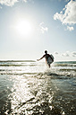 France, Brittany, Camaret-sur-Mer, teenage boy with surfboard at the ocean - UUF001665