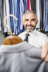 Portrait of businessman choosing jacket at his walk-in closet - MBEF001192