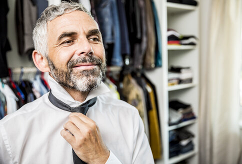 Portrait of smiling businessman binding tie at his walk-in closet - MBEF001196