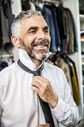 Portrait of smiling businessman binding tie at his walk-in closet - MBEF001197