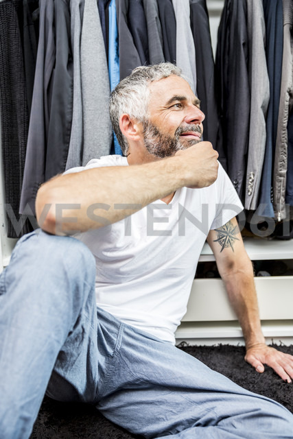Smiling man sitting on the floor of his walk-in closet - MBEF001204 - Martin Benik/Westend61