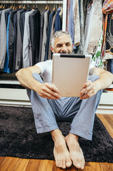 Man with his digital tablet sitting on the floor of his walk-in closet - MBEF001207
