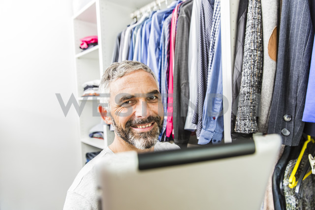 Man with his digital tablet standing at his walk-in closet - MBEF001209 - Martin Benik/Westend61