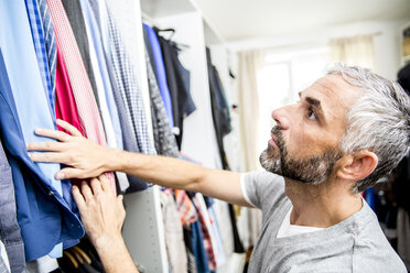 Man choosing clothes at his walk-in closet - MBEF001215