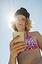 Teenage girl using her smartphone on the beach - UUF001692