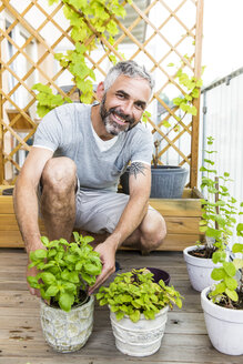 Portrait of smiling man gardening on his balcony - MBEF001104