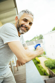 Portrait of smiling man relaxing with cup of coffee on his balcony - MBEF001114