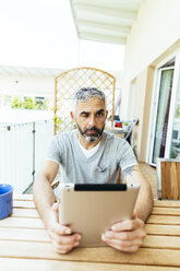 Portrait of man with digital tablet sitting on his balcony - MBEF001117