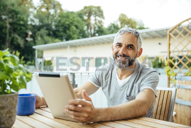 Portrait of smiling man sitting on his balcony using digital tablet - MBEF001119 - Martin Benik/Westend61