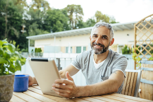 Portrait of smiling man sitting on his balcony using digital tablet - MBEF001119